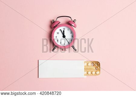 Female Oral Contraceptive Pills Blister With Alarm Clock On Pink Background. Women Contraceptive Hor