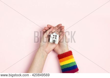 Female Hands With Lgbt Wristband Hold A Toy House On Pink  Background. Tolerance To Homosexual And B