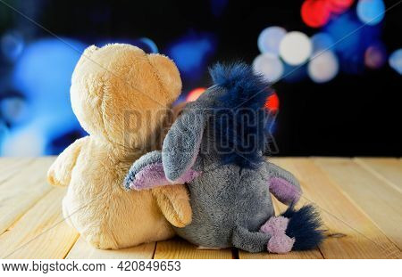 Two Teddy Bears Hugging Their Backs On A Wooden Table And Defocused Lights Background. Tender Friend