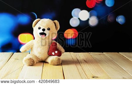 Teddy Bear Cuddled On His Back On A Wooden Table And Defocused Lights Background With A Stuffed Hear