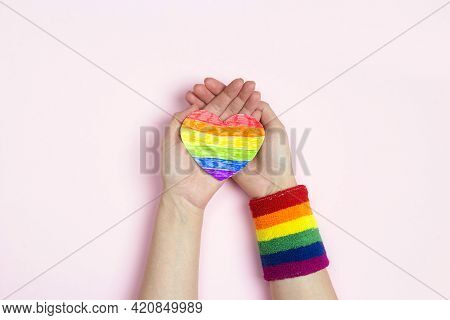 Female Hands Hold Rainbow Lgbt Heart On A Pink Background. Homosexual And Lgbt Concept.
