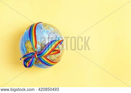 Globe With Lgbt Rainbow Ribbon On Yellow Background. Lgbt Community. Homosexual People Concept.