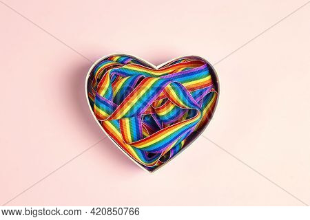 Lgbt Rainbow Ribbon In A Heart Shape On Pink Background. Pride Tape Symbol.