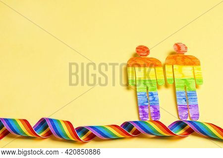 Gay Couple Figures With Lgbt Rainbow Ribbon On Yellow Background. Lgbt Pride.  Lgbt Equal Rights Mov