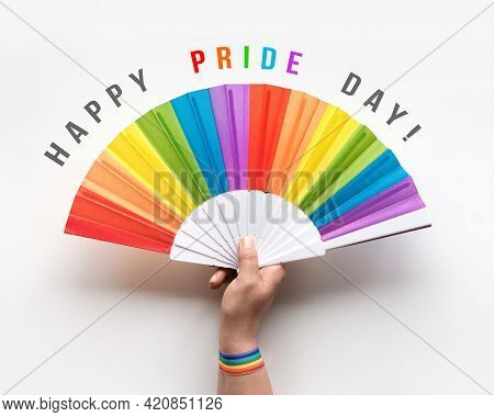 Happy Pride Day Hand Holds Rainbow Fan. Ribbon With Rainbow Design On Wrist. Flat Lay, Top View On O