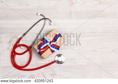 Stethoscope And Gift Box With Russian Flag Color Ribbon On Light Wooden Background. Russian Medical