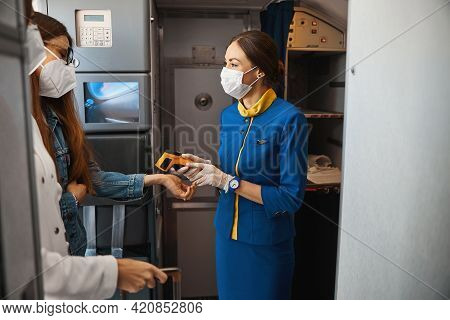 Cabin Attendant Measuring Woman Temperature With Infrared Thermometer