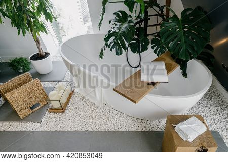 High Angle View On Modern White Bathtub And Wooden Shelf With Book. Beautiful Dream Boho Style Bathr