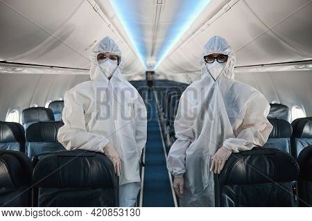 Two Cabin Crew Workers In Protective Overalls In Plane Cabin