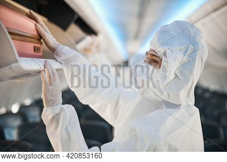 Flight Attendant In Safety Coverall Hiding Luggage In Overhead Bin