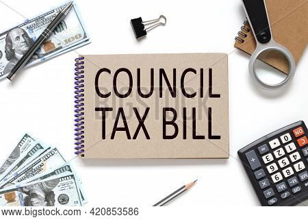Council Tax Bill . Business Concept. Notebook On White Workspace. Near The Notepad Dollar Bills And
