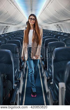Stylish Female In Blazer Walking Through Plane Aisle