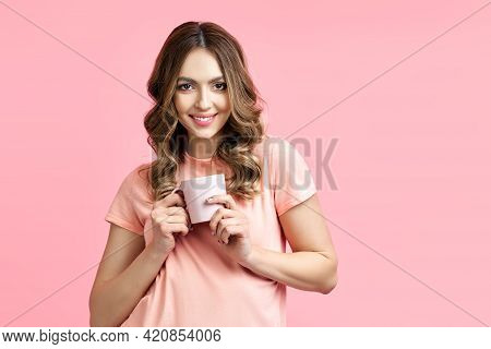 Smiling Pretty Woman Enjoying Cup Of Aroma Coffee On Pink Background