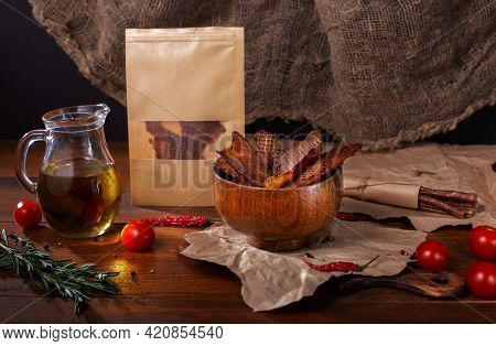 Jerky Snacks In Wooden Bowl, Olive Oil In Glass Jug, Meat Sticks, Red Pepper, Cherry Tomatoes And Ro