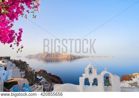 White Church Belfry Over Sea And Caldera, Santorini Island With Flowers, Greece