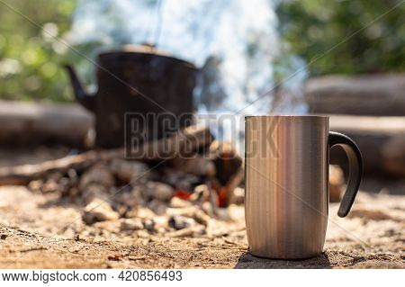 Metal Mug With A Hot Drink Stands On The Ground, Against The Background Of A Campfire With A Kettle,
