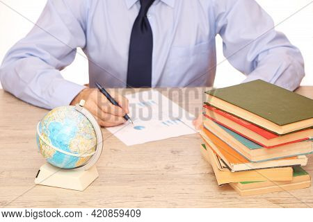 A Businessman In A Blue Shirt In The Office Writes A Report, On The Table A Globe, Books And Glasses