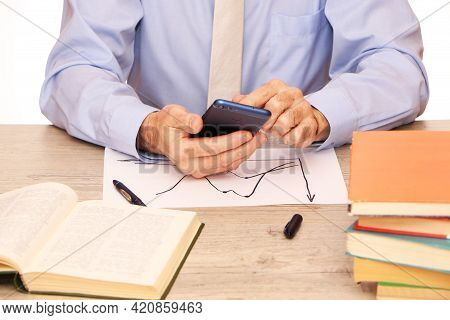 A Businessman In A Blue Shirt And Beige Tie In The Office Holds A Smartphone In His Hand, A Globe, B