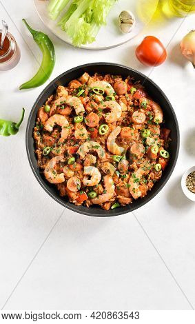 Creole Jambalaya With Chicken, Smoked Sausages And Vegetables In Frying Pan On White Stone Backgroun