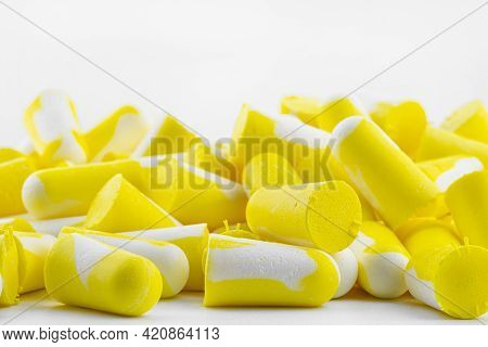 Macro Shots Of Multiple Earplugs In Yellow And White For Noise Protection, Isolated On White Backgro