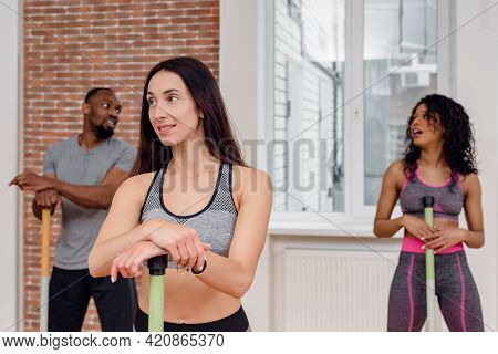 Multinational Group Of Athletes Doing Fitness Exercise With Bars In Modern Gym