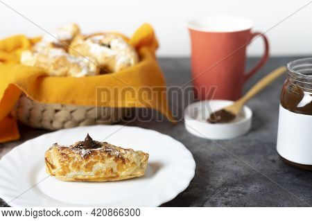 Chocolate-filled Puff Pastry Neapolitan With Basket Of Puff Pastry Sweets, Coffee Cup, Open Jar Of C