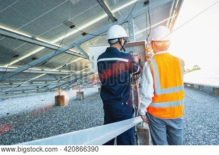 Workers Use Clamp Meter To Measure The Current Of Electrical Wires Produced From Solar Energy For Co
