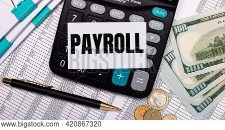 On The Desktop Are Reports, A Pen, Cash, A Calculator And A Card With The Text Payroll. Business Con