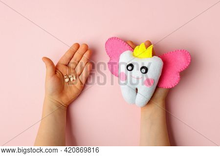 Felt Tooth Fairy Pillow And Milk Tooth In Kids Hands On Pink Background With Copy Space For Text. Ha