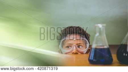Composition of african american boy in lab with flasks, wearing goggles with motion blur. science and research technology concept digitally generated image.