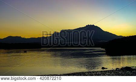Silhouette Of Mount Kinabalu At Sunrise From Mengkabong River,tuaran,sabah Borneo,malaysia. Its The