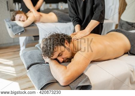 Beautiful Couple Lying In A Spa Salon Enjoying Getting Deep Back Massage And Relaxation. Wellness An