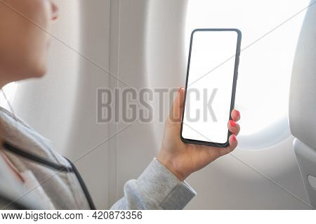 Woman Hand Holding Smart Cell Phone With Blank White Screen On Board Of Airplane Near Window Seat. W
