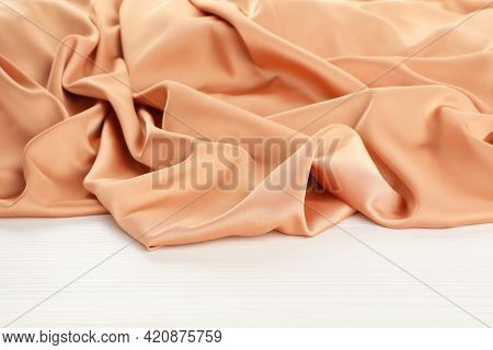 Beautiful Delicate Peach Silk On White Wooden Table