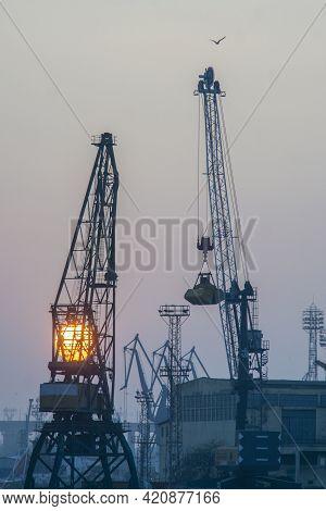 Sunset With Industrial Shipyard Cranes Vertical Shot