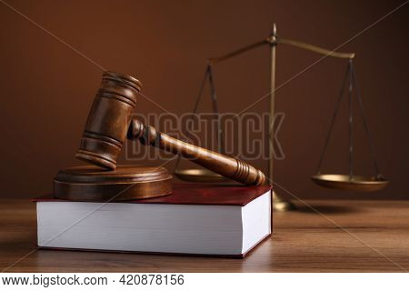 Judge's Gavel With Sound Block, Scales Of Justice And Book On Wooden Table Against Brown Background