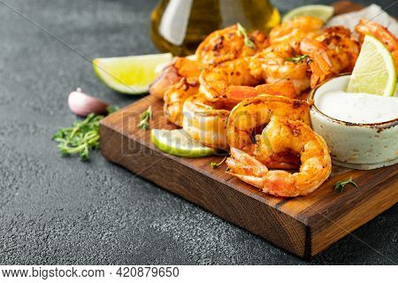 Grilled Shrimps Or Prawns Served With Lime, Garlic And White Sauce On A Dark Concrete Background. Se
