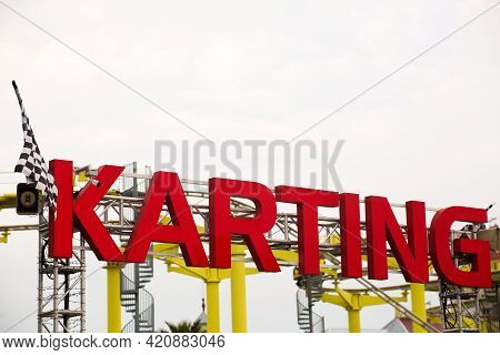 A Sign For Go-carting Over The Road, Karting Word In Red Is Voluminous.