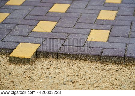 laying paving slabs in a city street, pavement tile closeup