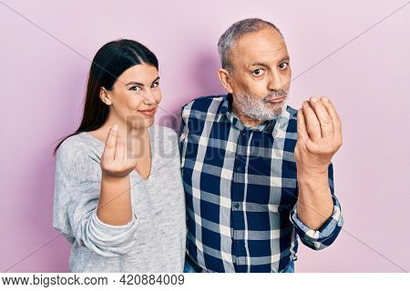 Hispanic father and daughter wearing casual clothes doing money gesture with hands, asking for salary payment, millionaire business