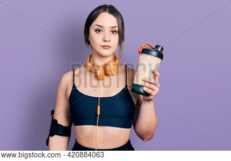 Young hispanic girl wearing sport clothes drinking a protein shake thinking attitude and sober expression looking self confident