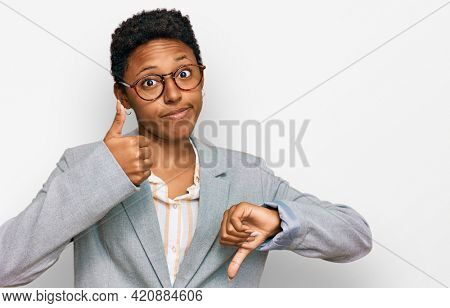 Young african american woman wearing business clothes doing thumbs up and down, disagreement and agreement expression. crazy conflict