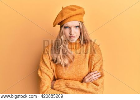 Beautiful young caucasian girl wearing french look with beret skeptic and nervous, disapproving expression on face with crossed arms. negative person.