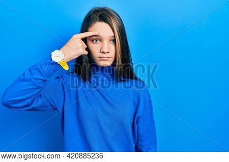 Young brunette girl wearing turtleneck sweater pointing unhappy to pimple on forehead, ugly infection of blackhead. acne and skin problem