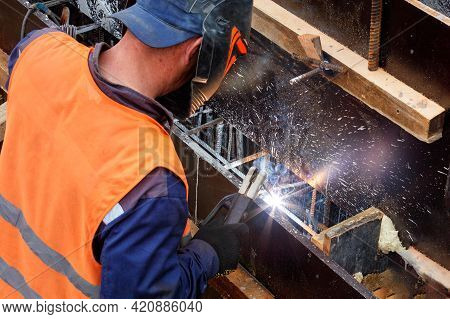 A Welder In A Protective Helmet And Gloves Using An Electrode Welds Metal Rods At A Construction Sit
