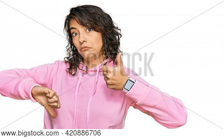Young hispanic woman wearing casual sweatshirt doing thumbs up and down, disagreement and agreement expression. crazy conflict