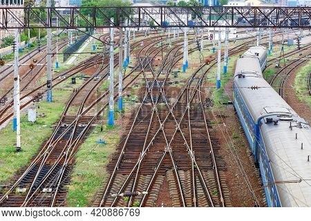 Extensive Multichannel Rail Network For Trains In The Springtime, Blue Carriages Of A Departing Trai