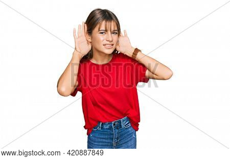 Teenager caucasian girl wearing casual red t shirt trying to hear both hands on ear gesture, curious for gossip. hearing problem, deaf