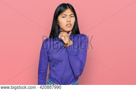 Beautiful young asian woman wearing casual clothes touching painful neck, sore throat for flu, clod and infection