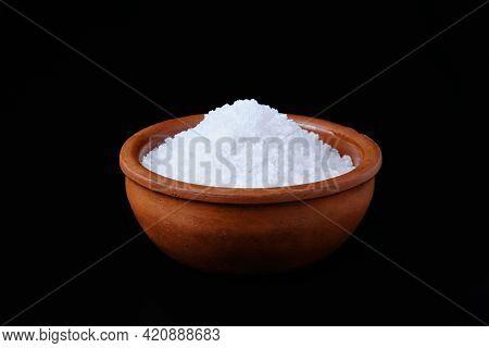 Sea Salt Crystals In Brown Crockery Against Black Background. Mineral Bath Rock Salt.